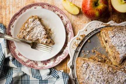 Imagen de arriba de una rebanada de pastel de café con crema agria de manzana, con todo el pastel a un lado.