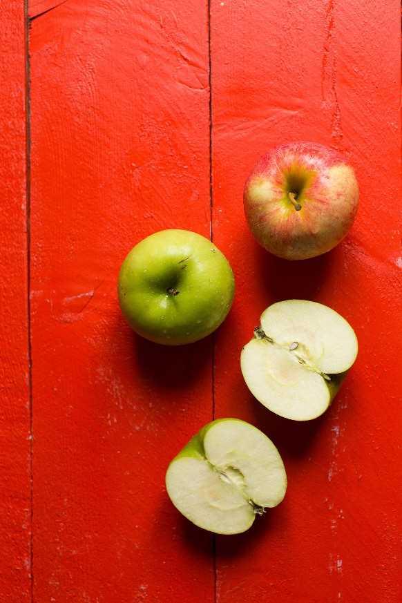 Manzanas frescas sobre un fondo rojo para una receta vegana de barras de crumble de pastel de manzana sin gluten