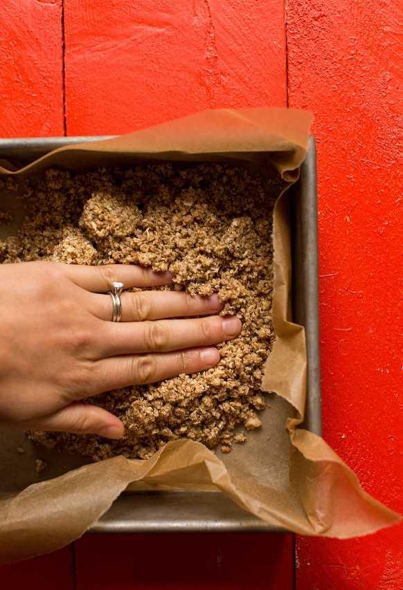 Al presionar los ingredientes de la corteza de avena y almendras en una bandeja para hornear forrada de pergamino para obtener barras de pastel de manzana veganas sin gluten