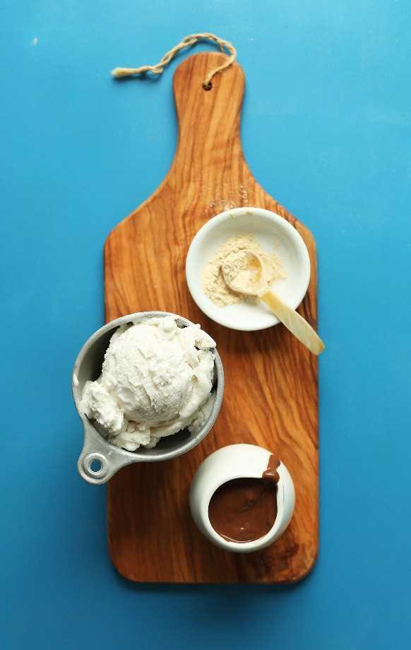 Tabla de cortar de madera con maca, helado vegano y salsa de chocolate para hacer una malta vegana de chocolate