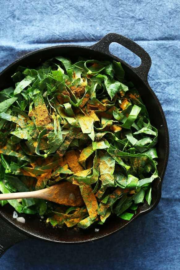 Collard greens y curry en polvo en una sartén de hierro fundido lista para convertirse en una deliciosa guarnición vegana