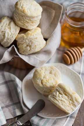 Imagen de primer plano de galletas caseras de suero de leche en un paño a cuadros, con un tarro de miel en el fondo.