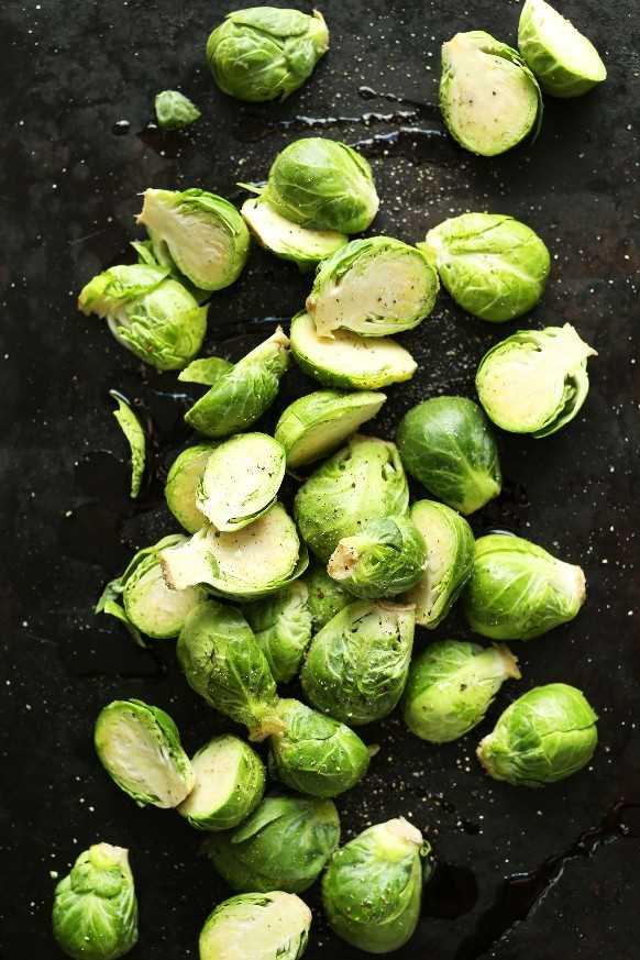 Bandeja para hornear con Bruseels Sprouts listos para asar para una comida a base de plantas sin gluten