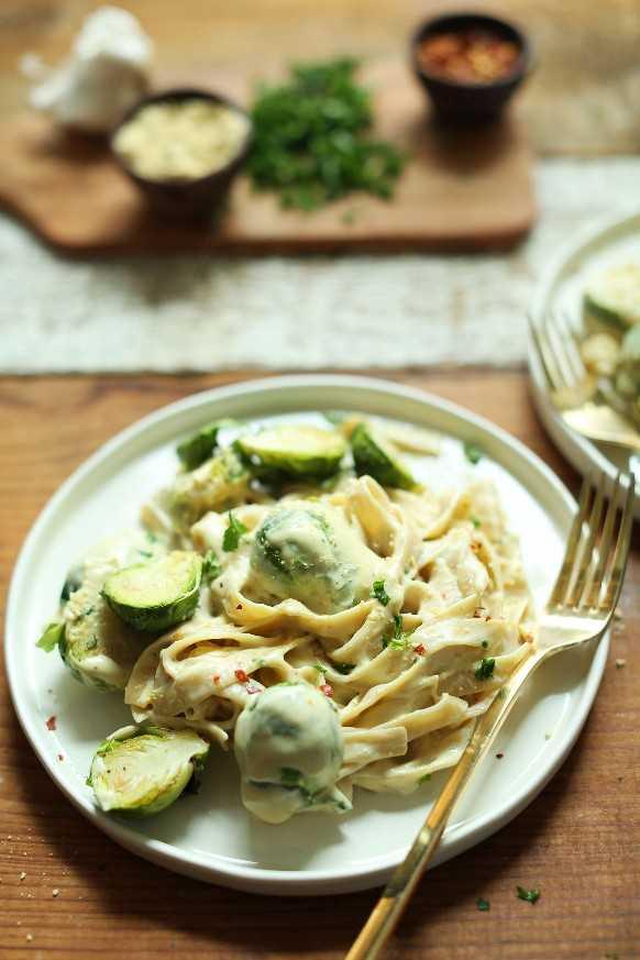 Abundante porción de nuestra receta reconfortante de ajo vegano Alfredo Pasta con coles de Bruselas asadas
