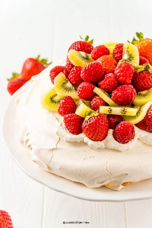Feche a foto de um pavlova coberto com morangos, framboesas e kiwi em um carrinho de bolo branco.