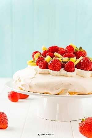 Pavlova sobre un soporte de pastel blanco cubierto con bayas frescas y kiwi.