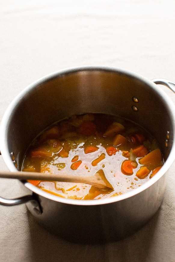 Olla de sopa llena de ingredientes para hacer sopa vegana de calabaza de bellota sin gluten para Acción de Gracias
