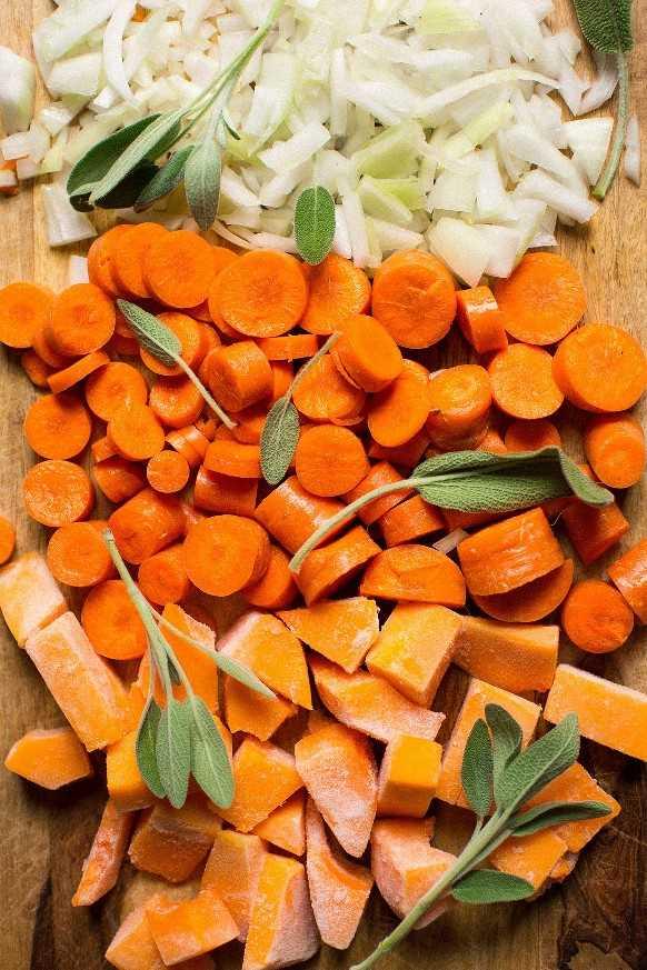 Tabla de cortar con cebollas, zanahorias, calabaza y salvia para hacer sopa de bellota