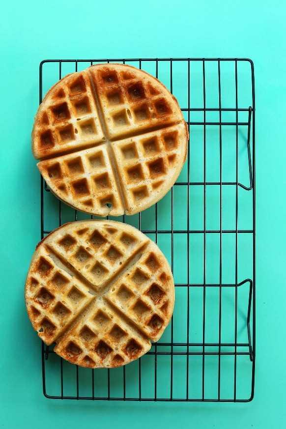 Dos waffles veganos sin gluten perfectamente dorados en una rejilla para enfriar