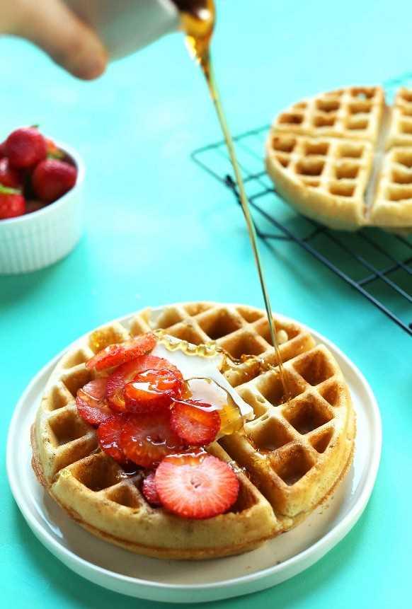 Verter el jarabe sobre waffles veganos sin gluten crujientes por fuera y esponjosos por dentro