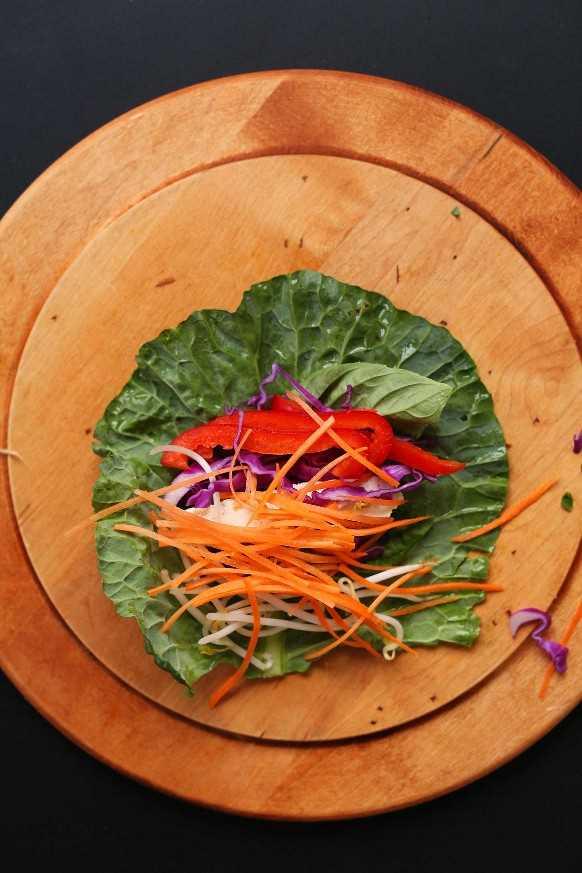 Tabla de cortar de madera con hojas de col verde e ingredientes frescos para hacer rollitos de primavera a base de plantas.