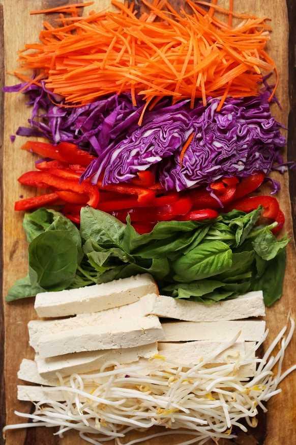 Zanahorias ralladas, repollo, pimiento, albahaca, tofu y brotes de soja para hacer rollos de ensalada vegana casera