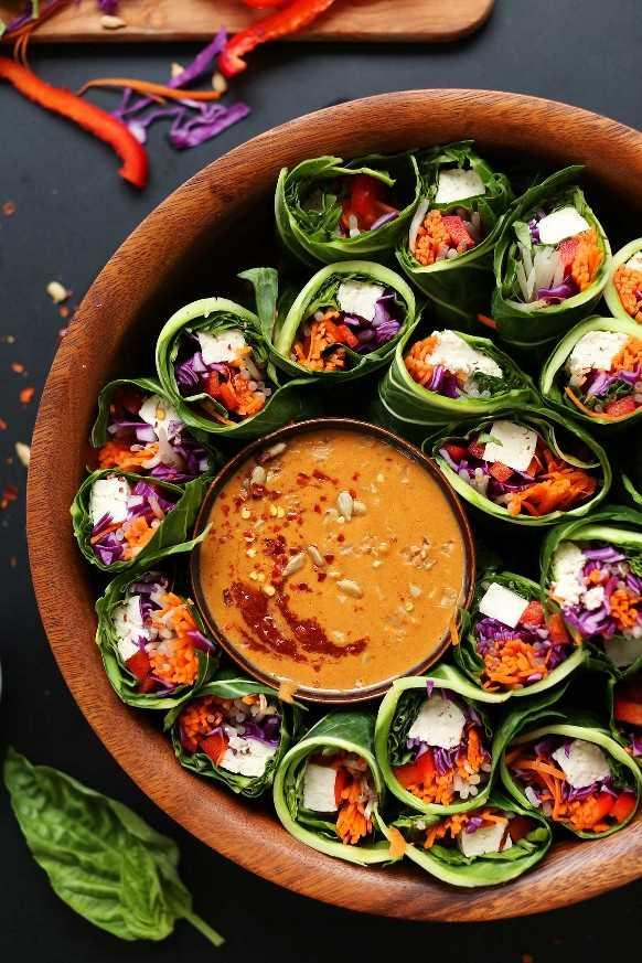 Cuenco lleno de increíbles rollitos de primavera Collard Green, Veggie y Tofu con salsa de mantequilla de Sunbutter para una sabrosa comida a base de plantas