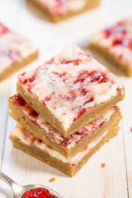 Barras de Cheesecake de Morango - Barras suaves e amanteigadas cobertas com cheesecake e redemoinhos de geléia de morango! O melhor de todos os mundos nestes bares rápidos, fáceis e INCRÍVEIS!