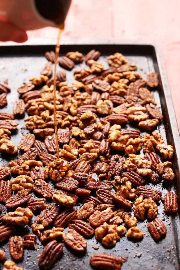 Verter jarabe sobre nueces para nuestra idea casera de regalo de vacaciones de nueces confitadas asadas