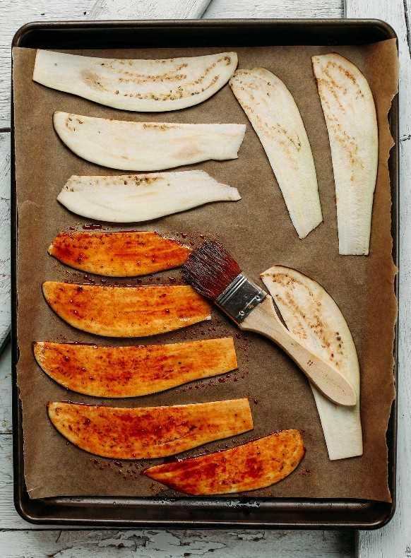 Cepille la salsa sobre la berenjena en rodajas que se coloca sobre una bandeja para hornear forrada