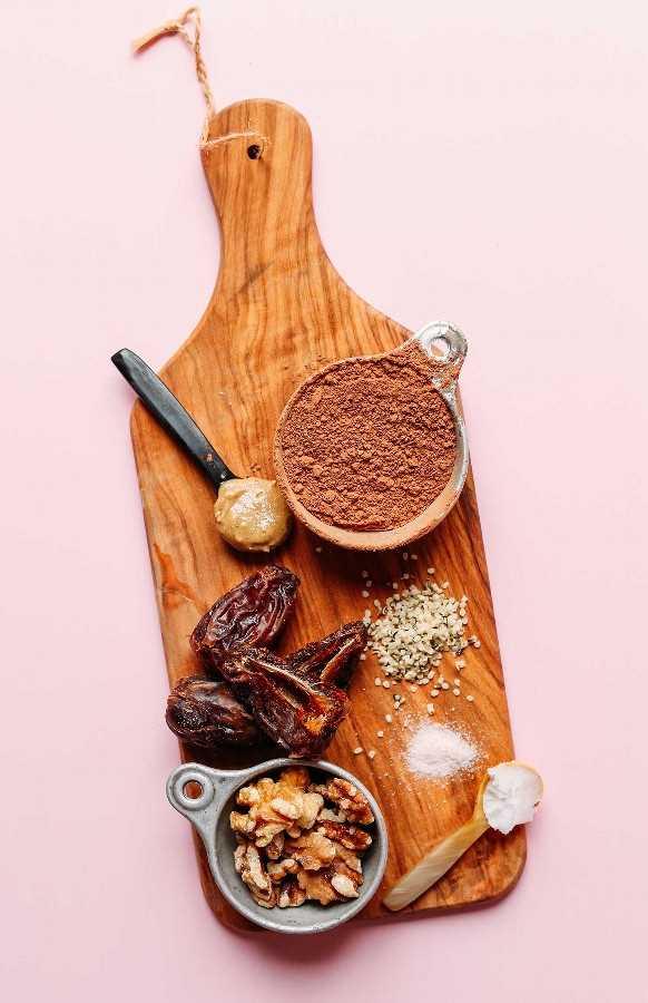Tablero de madera con nueces, dátiles, mantequilla de nueces, cacao en polvo, semillas de cáñamo, sal y aceite de coco para hacer bocados de chocolate con cáñamo