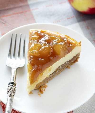 Una rebanada de pastel de queso con manzana y caramelo