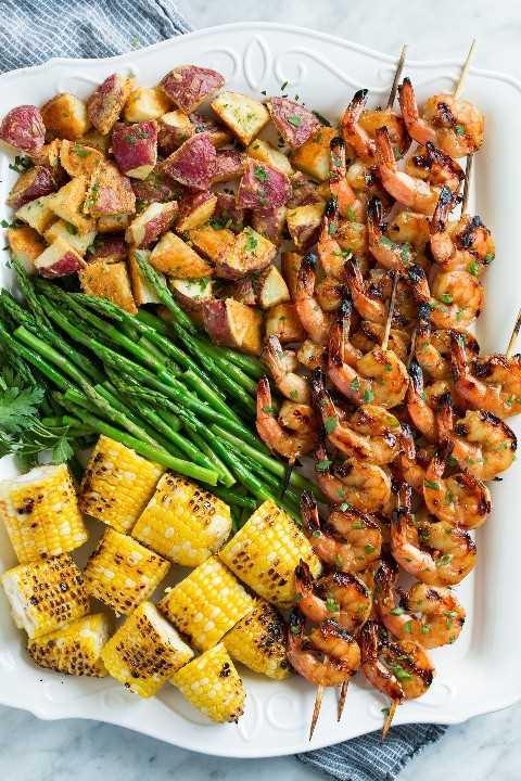 Plato lleno de camarones a la parrilla, maíz a la parrilla, espárragos y papas asadas.