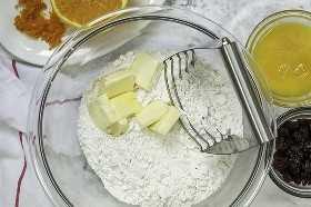La mantequilla en rodajas se corta en la harina.