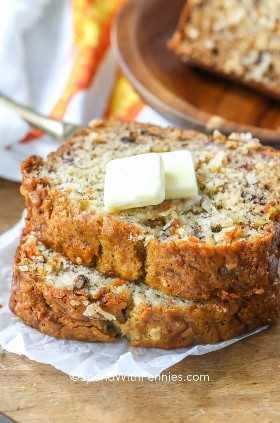Duas fatias de pão de banana e cenoura com um pouco de manteiga por cima.
