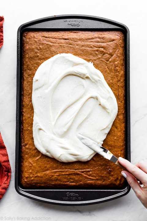 esparciendo glaseado de queso crema sobre una bandeja de barras de calabaza