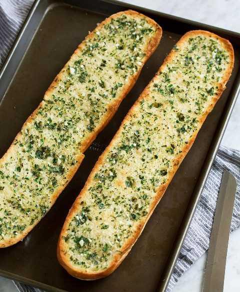 Dos mitades de pan de ajo en una bandeja para hornear oscura. Se muestra después del tostado.