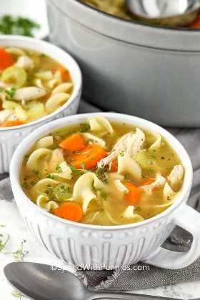 Dos tazones de sopa de pollo con fideos.