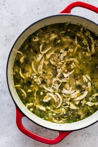 Green Chicken Chili en un horno holandés cubierto con cilantro.