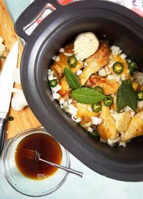 Descripción general de una olla de cocción lenta con ingredientes de adobo de pollo dentro.