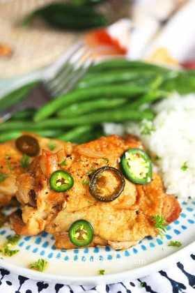 Una porción de pollo adobo en un plato con arroz y judías verdes.