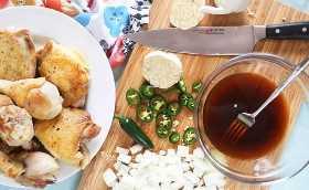 Ingredientes de pollo Adobo en una tabla de cortar junto a un plato de pollo chamuscado.