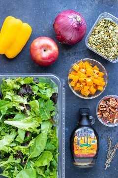 Ensalada mixta de verduras, manzana, semillas de calabaza, nueces, pimiento y cebolla como los ingredientes en una receta de ensalada de otoño.