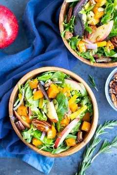 Dos cuencos llenos de una saludable y vegana ensalada de cosecha de otoño con manzanas y nueces.
