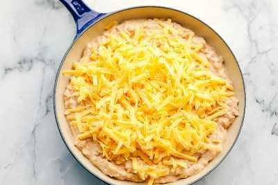 mezcla de frijoles con queso encima en la sartén de hierro fundido lista para entrar en el horno