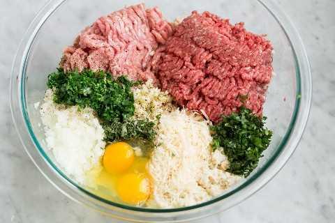 Carne molida de res, carne molida de cerdo, hierbas frescas, parmesano, huevos, cebolla, ajo y pan rallado empapado en un tazón de vidrio.