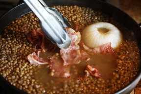 Agregar tocino a la sopa de lentejas que se cocina en la estufa
