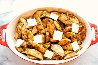 canela con azúcar morena manzanas al horno en hierro fundido con mantequilla encima preparándose para hornear.