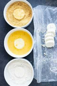 Tres tazones de pan rallado, harina y huevos junto a los medallones de queso de cabra que muestran cómo hacer queso de cabra frito.