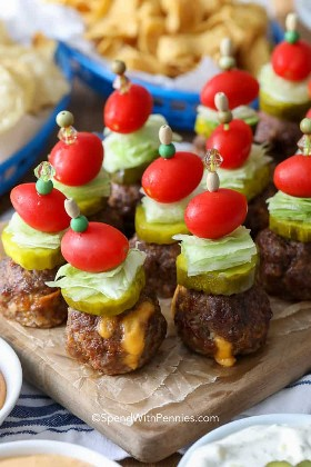 Feche de almôndegas recheadas com cheeseburger, picles com picles, alface e tomate em uma placa de corte.