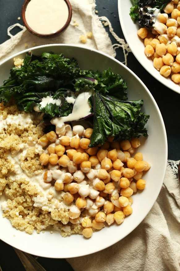 Porciones de nuestros cuencos de Buda de garbanzos y quinua con salsa de col rizada y tahini para una deliciosa comida a base de plantas