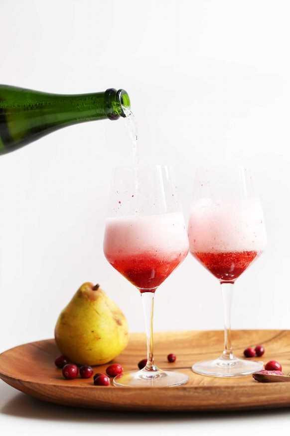 Verter champán para nuestras mimosas de champán de 5 ingredientes con reducción de arándano y pera