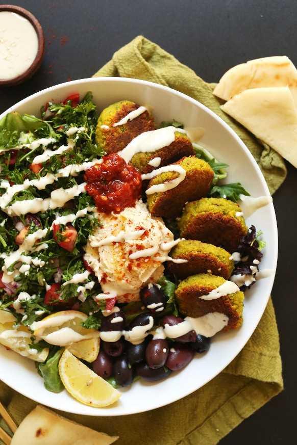 Sirviendo nuestro tazón mediterráneo vegano con hummus, falafel, salsa de tahini, aceitunas y pita