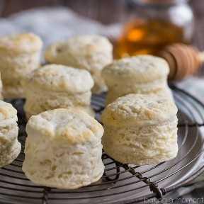 Cerrar imagen de un lote de galletas de suero de leche caseras altas y esponjosas en una rejilla de enfriamiento de alambre.