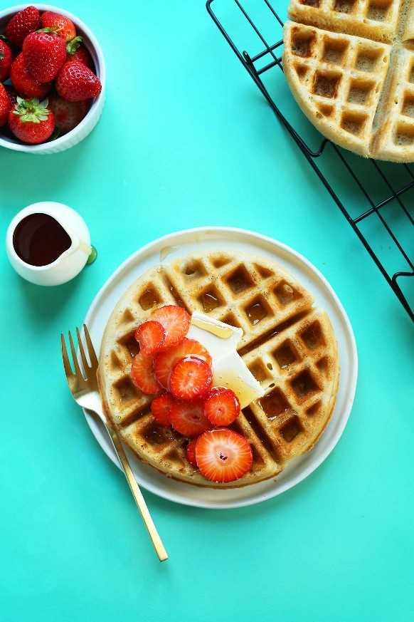 Plato con el gofre vegano sin gluten perfecto cubierto con jarabe, mantequilla vegana y fresas frescas