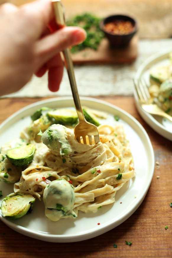 Girando un tenedor en un plato de vino blanco y ajo Alfredo Pasta con coles de Bruselas