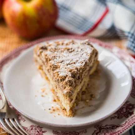 Rebanada de pastel de café de manzana en un plato rojo estampado, con manzanas frescas en el fondo.