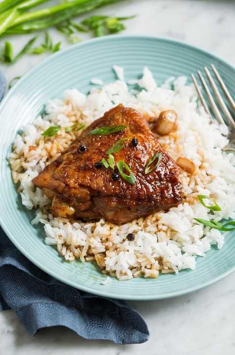 Coxa de frango marinada em um prato com arroz decorado com cebola verde.