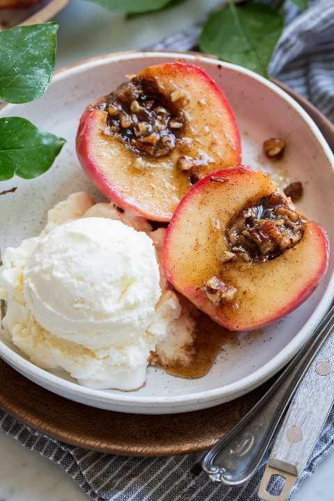 Manzana al horno en rodajas por la mitad mostrando el relleno de nuez de azúcar morena. Servido con un lado de helado de vainilla.
