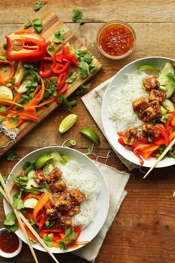 Dos tazones de fideos tailandeses con tofu crujiente de mantequilla de almendras junto con una tabla de cortar con ingredientes utilizados para preparar la receta